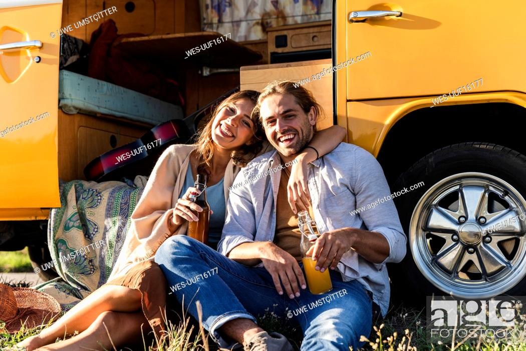 Photo de stock: Affectionate couple on a road trip, taking a break, drinking soft drinks.