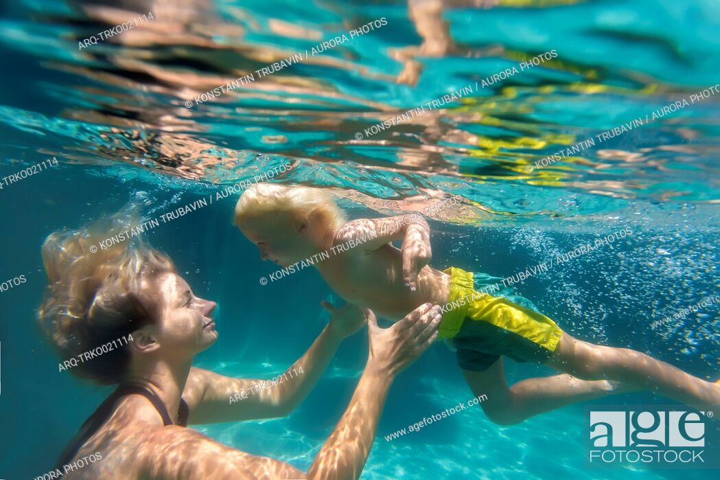 Stock Photo: Underwater view of mother and son swimming in swimming pool.