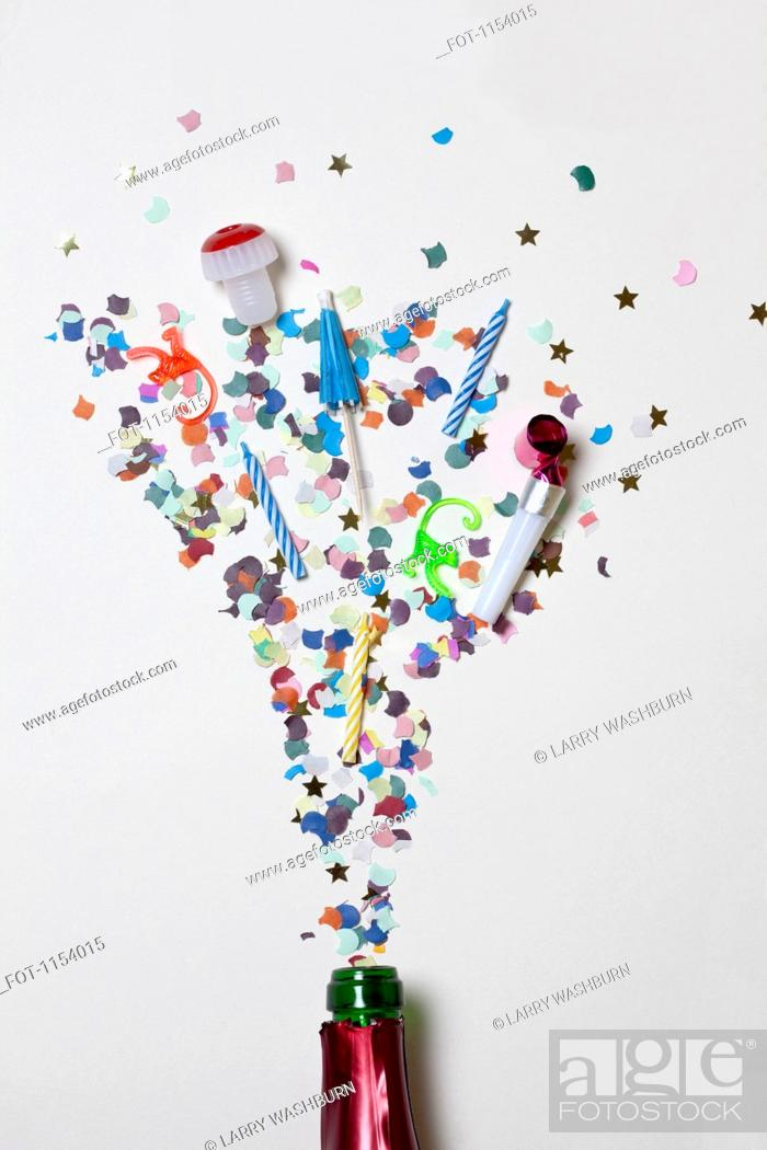 Stock Photo: Confetti and party supplies spraying out of a champagne bottle.