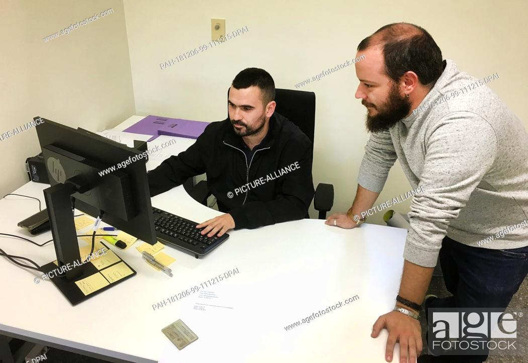 Photo de stock: 29 November 2018, Spain, Valencia: Vicent Galiana (l) and Alex Calpe work in the first office to advise and support dictatorship victims in Spain.