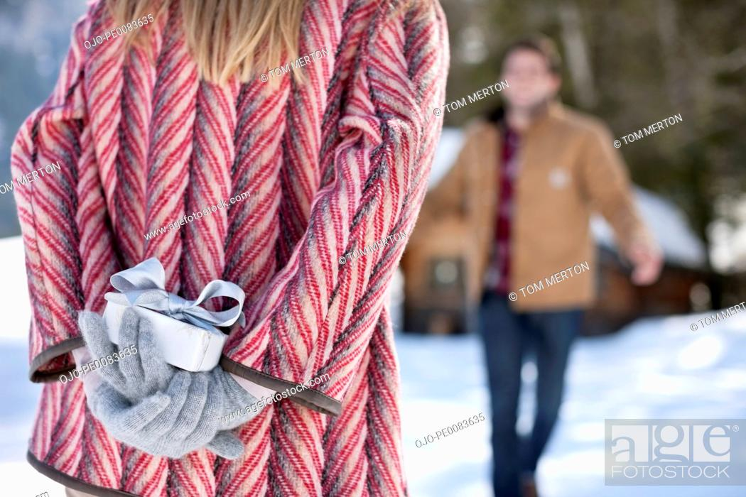 Stock Photo: Man approaching woman with Christmas gift behind back.