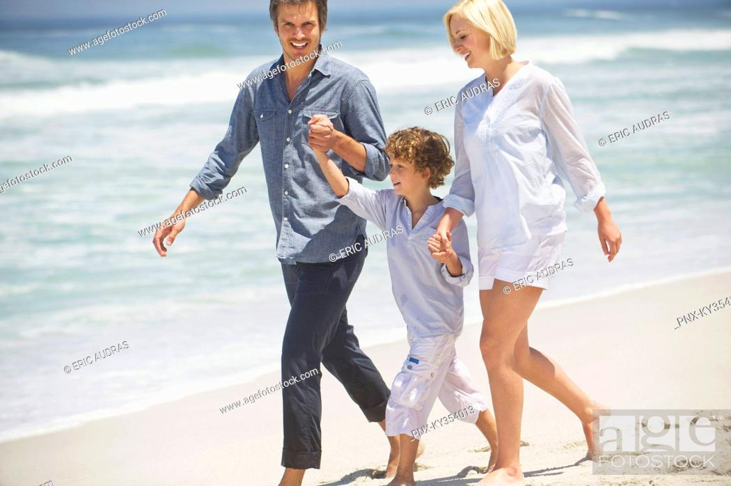Stock Photo: Couple with their son walking on the beach.