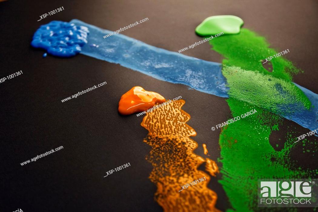 Stock Photo: Composición de tres colores de pintura: naranja, azul y verde / Composition of three paint colors: orange, blue and green.