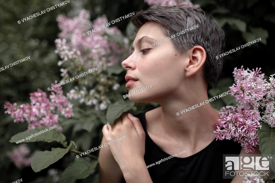 Stock Photo: Profile of Caucasian woman standing in flowers.