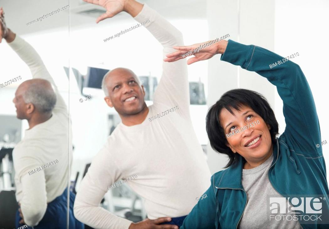 Stock Photo: African couple exercising in health club.