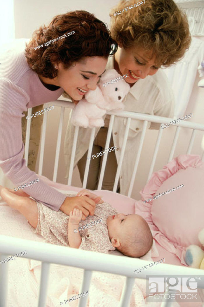 Stock Photo: Mother and grandmother playing with a baby girl.