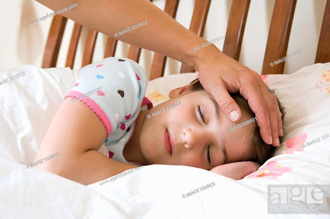 Stock Photo: Sleeping girl with adult hand on her head.