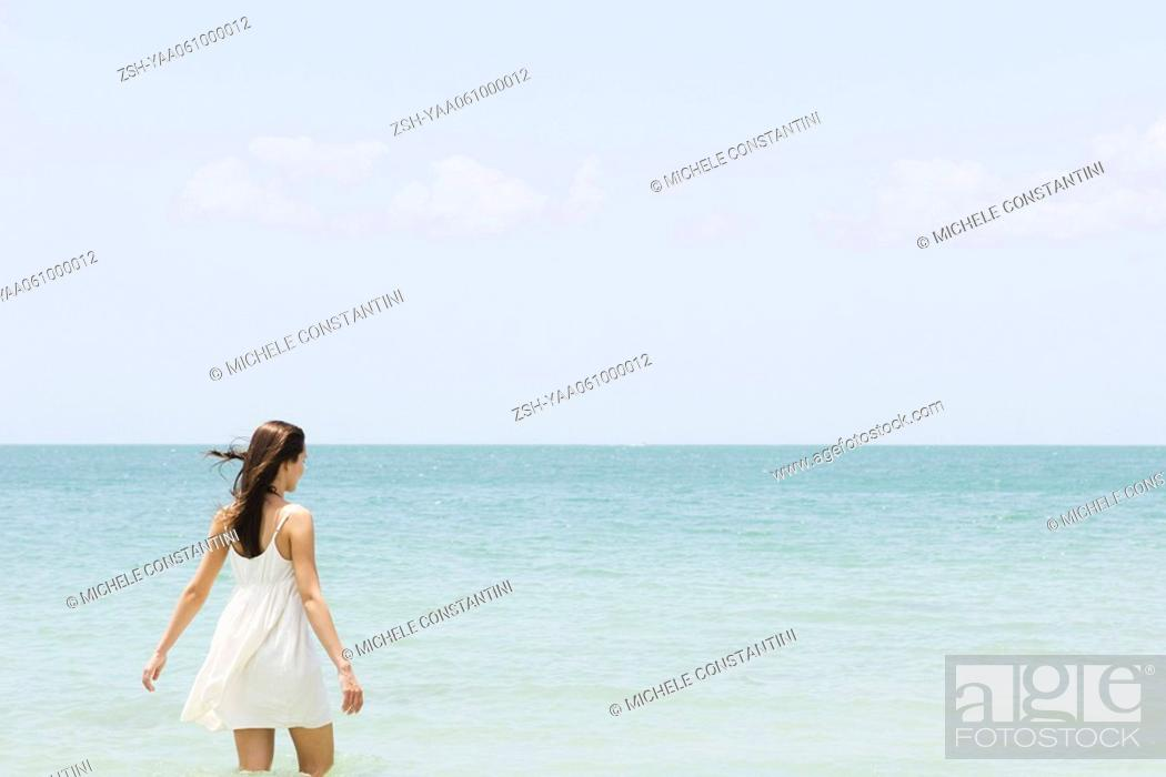 Stock Photo: Young woman in sundress standing knee deep in ocean, rear view.