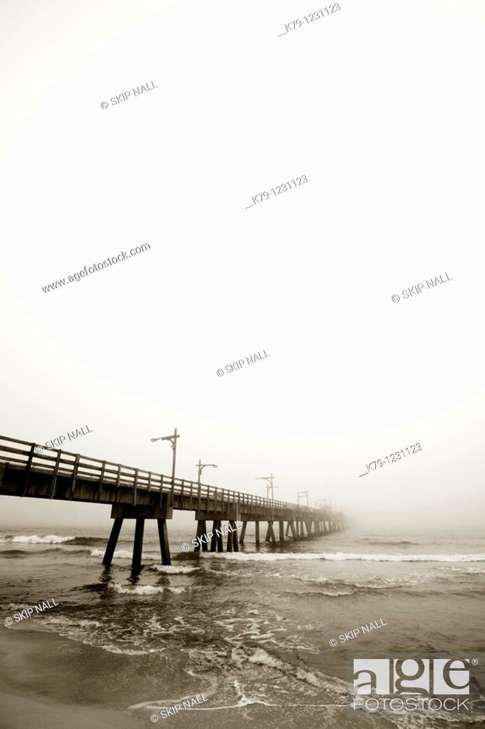Stock Photo: Pier at the beach on a cloudy day.