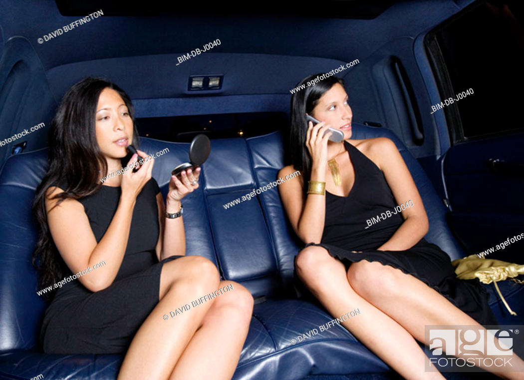 Stock Photo: Woman applying makeup while friend talks on cell phone in backseat of car.
