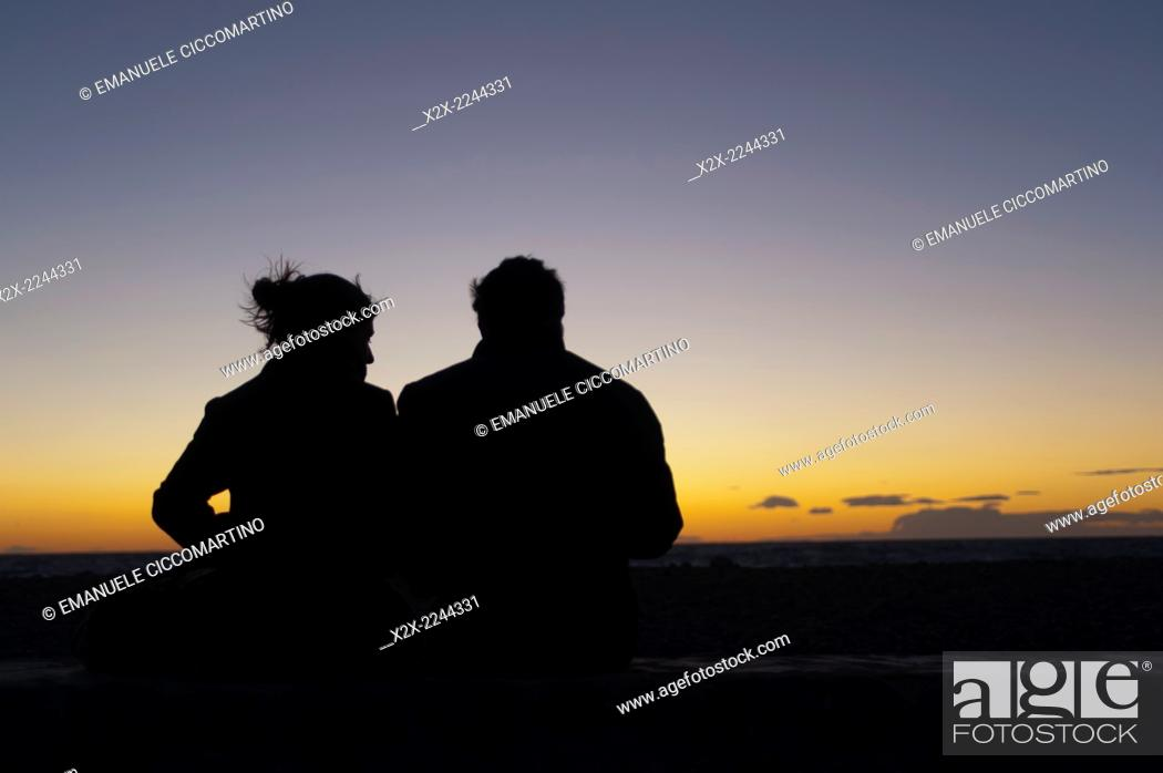 Stock Photo: Couple watching sunset, Es Codolar Boulder beach, Eivissa, Ibiza, Balearic Islands, Spain, Mediterranean, Europe.