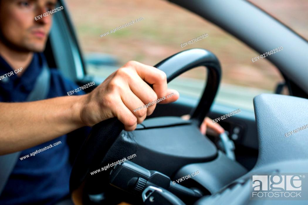 Stock Photo: Male driver's hands driving a car on a highway (color toned image; shallow DOF).