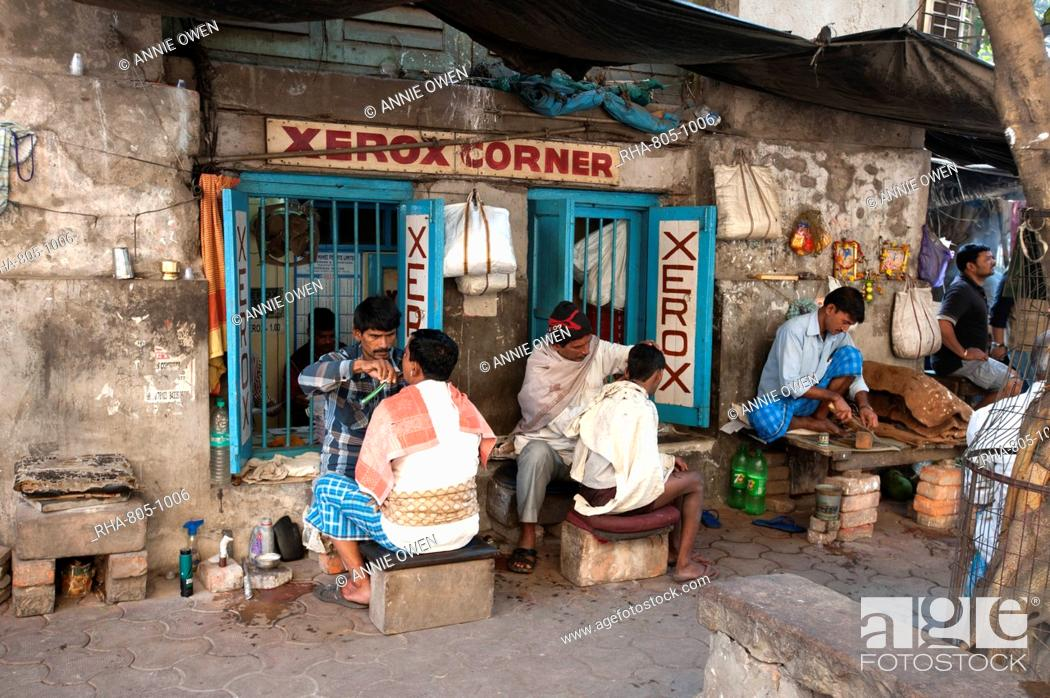 Stock Photo: Barbers cutting hair and shaving men, and tobacco wallah, in street stalls outside Xerox shop in Dalhousie Square area of Kolkata (Calcutta), West Bengal, India.