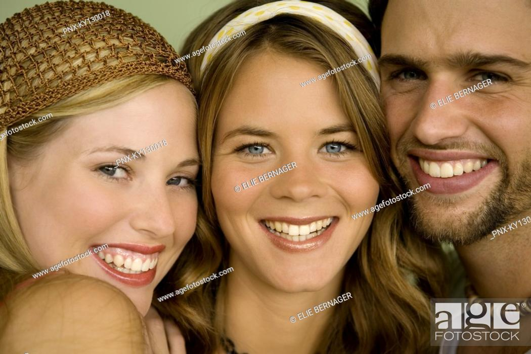Stock Photo: Portrait of 2 women and a man smiling for the camera.