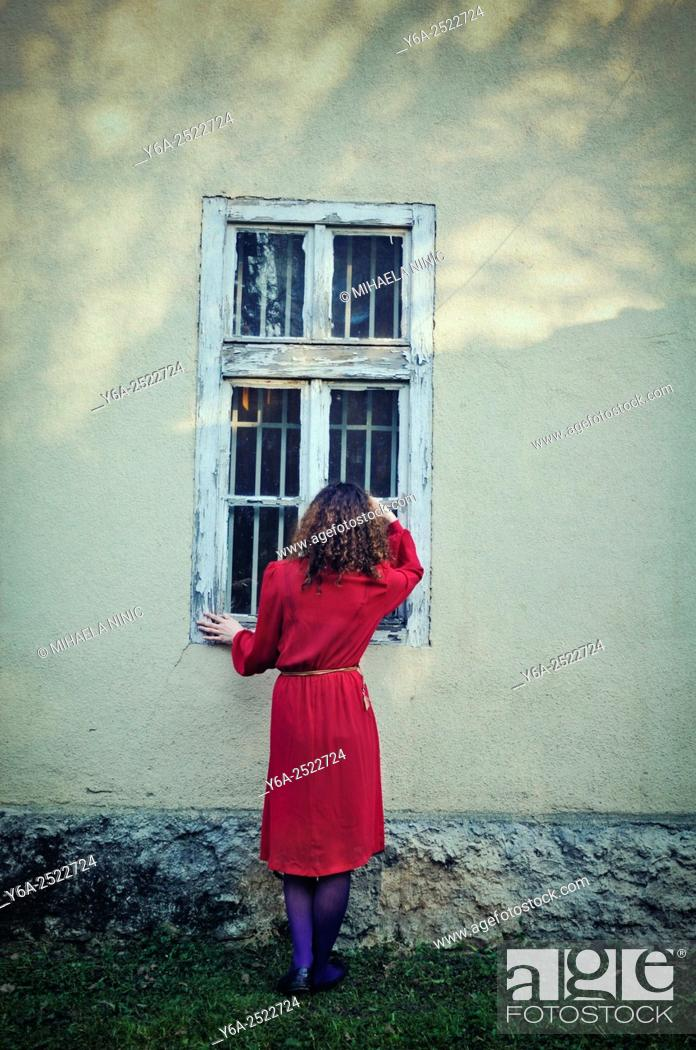Stock Photo: Woman standing outside the house looking through window.