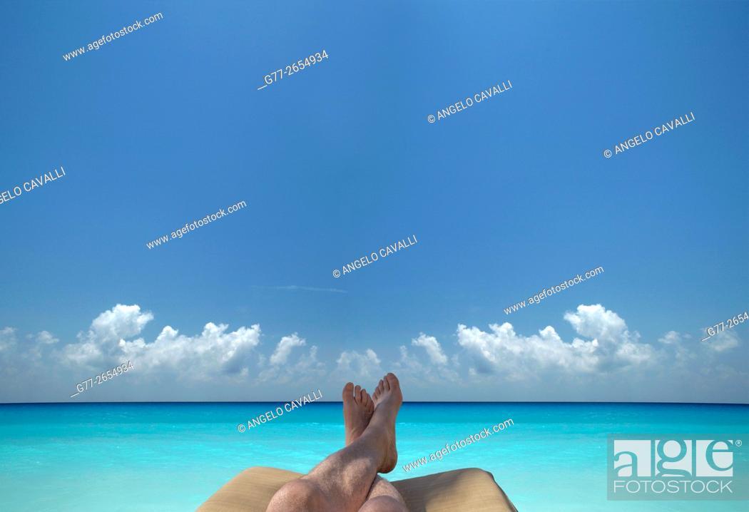 Imagen: Man feet on a beach chair on a beach over blue ocean.