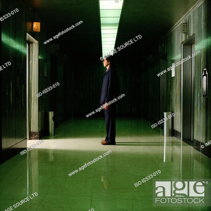 Stock Photo: Man standing in empty corridor.