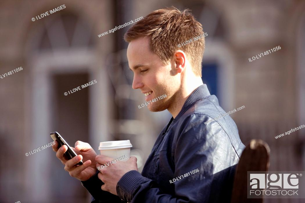 Stock Photo: A young man sitting on a bench, using his mobile phone.