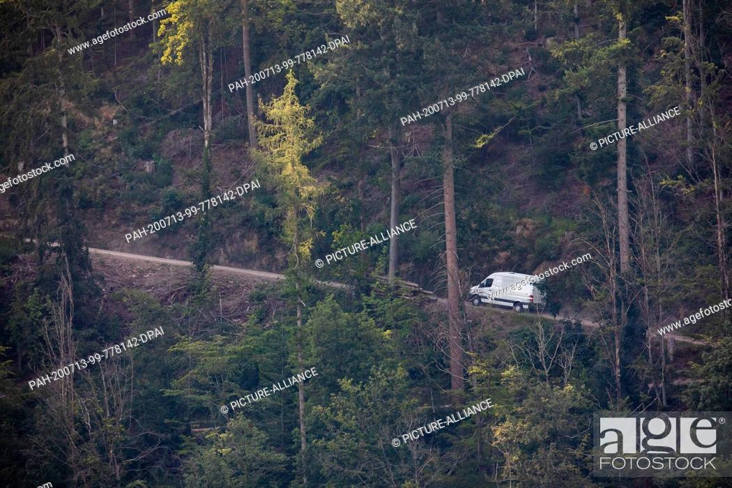 Stock Photo: 13 July 2020, Baden-Wuerttemberg, Oppenau: Police vehicles drive through the forest near Oppenau. With a large contingent.