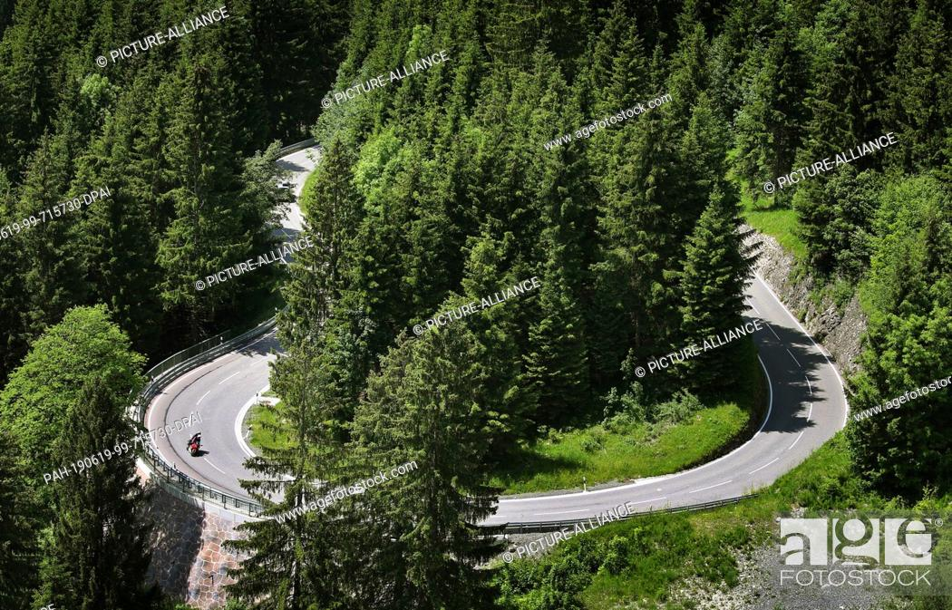 Stock Photo: 19 June 2019, Bavaria, Bad Hindelang: A motorbike rides on the Jochpass into a bend. During the summer months, the 106 curve pass with an altitude of 300 metres.