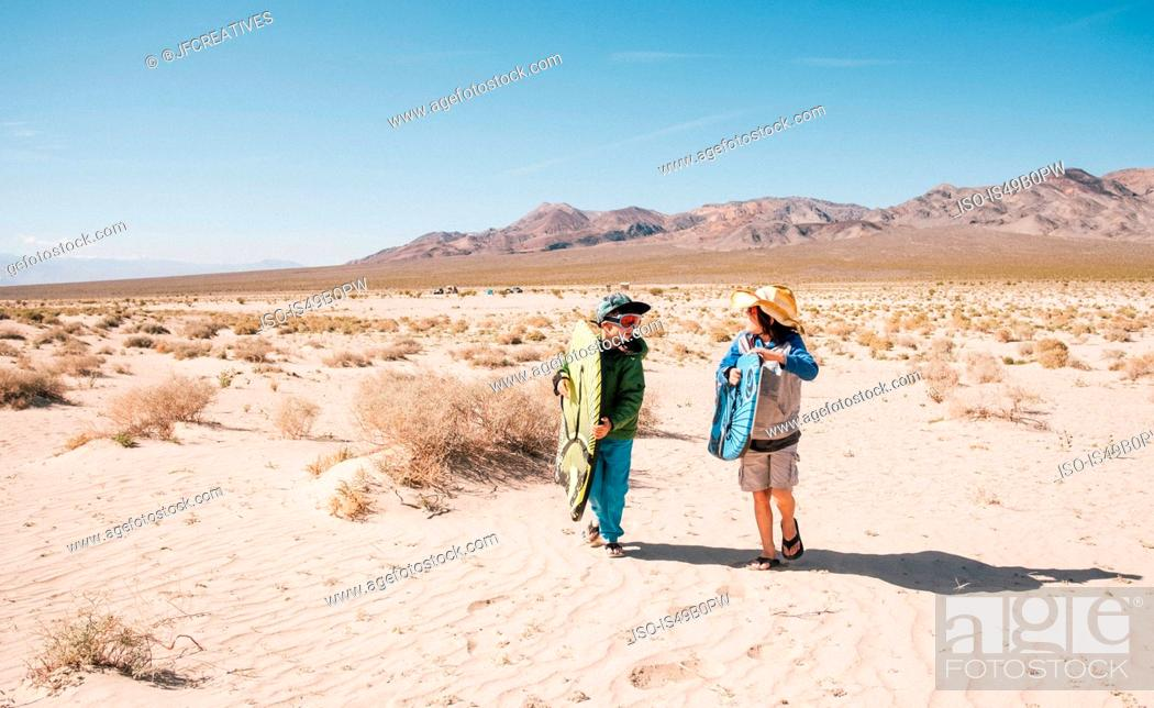 Stock Photo: Two boys walking together Eureka Dunes, Death Valley National Park, California, USA.