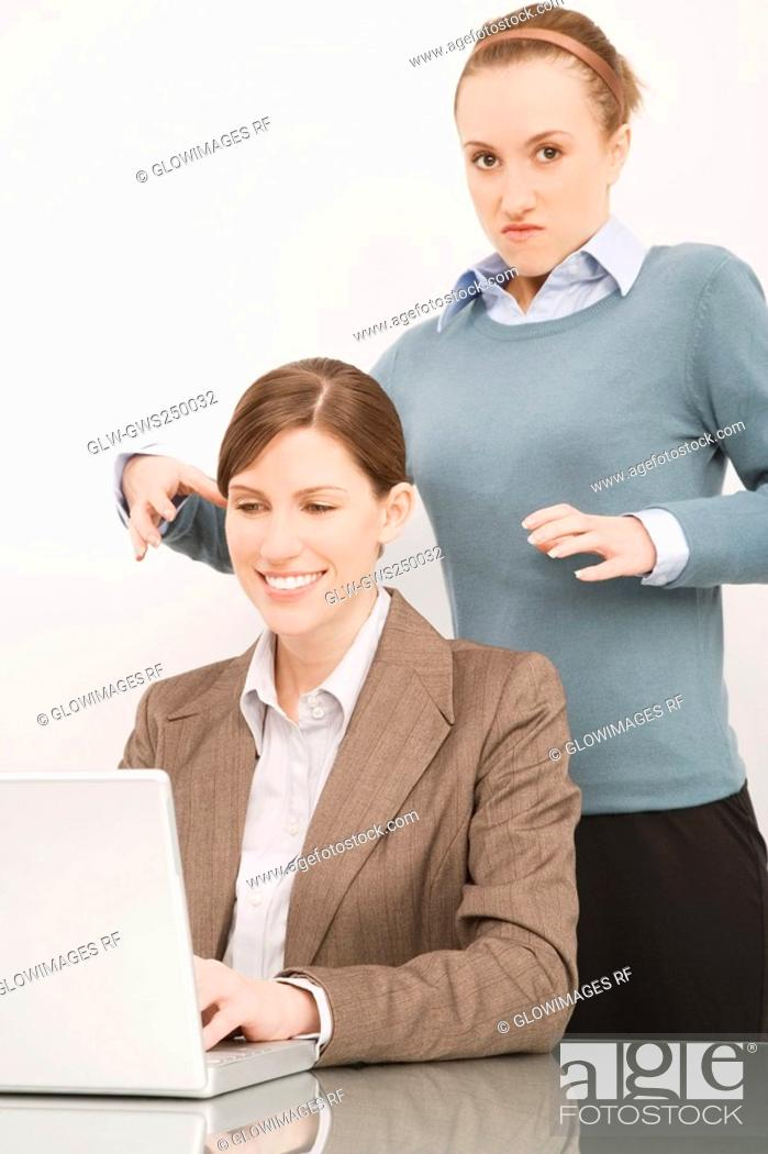 Stock Photo: Businesswoman working on a laptop with her colleague try to strangling behind her.