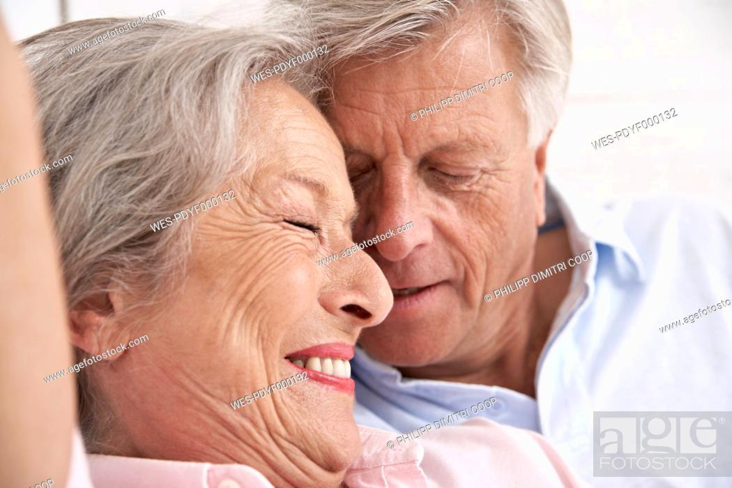 Stock Photo: Spain, Senior couple relaxing in hotel, smiling.