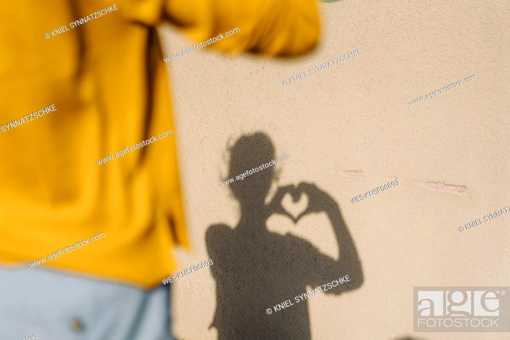 Stock Photo: Shadow of a woman shaping a heart with her hands.
