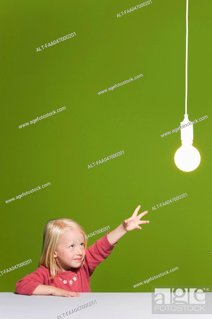 Stock Photo: Little girl reaching for illuminated light bulb suspended overhead.