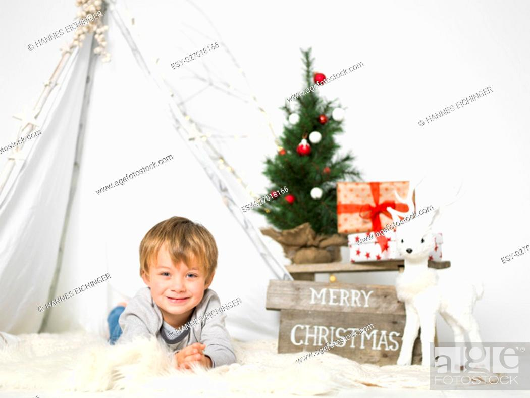 Stock Photo: christmas scene with blond young and small christmas tree.