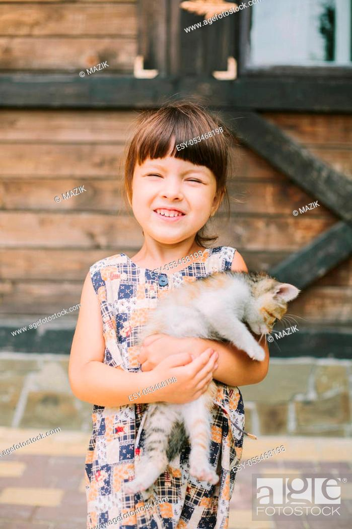 Stock Photo: happy little girl holding a cat in her arms.