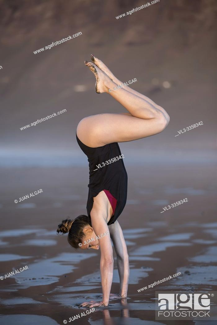 Stock Photo: Side view of slim woman in black bodysuit doing graceful handstand on wet sandy beach.
