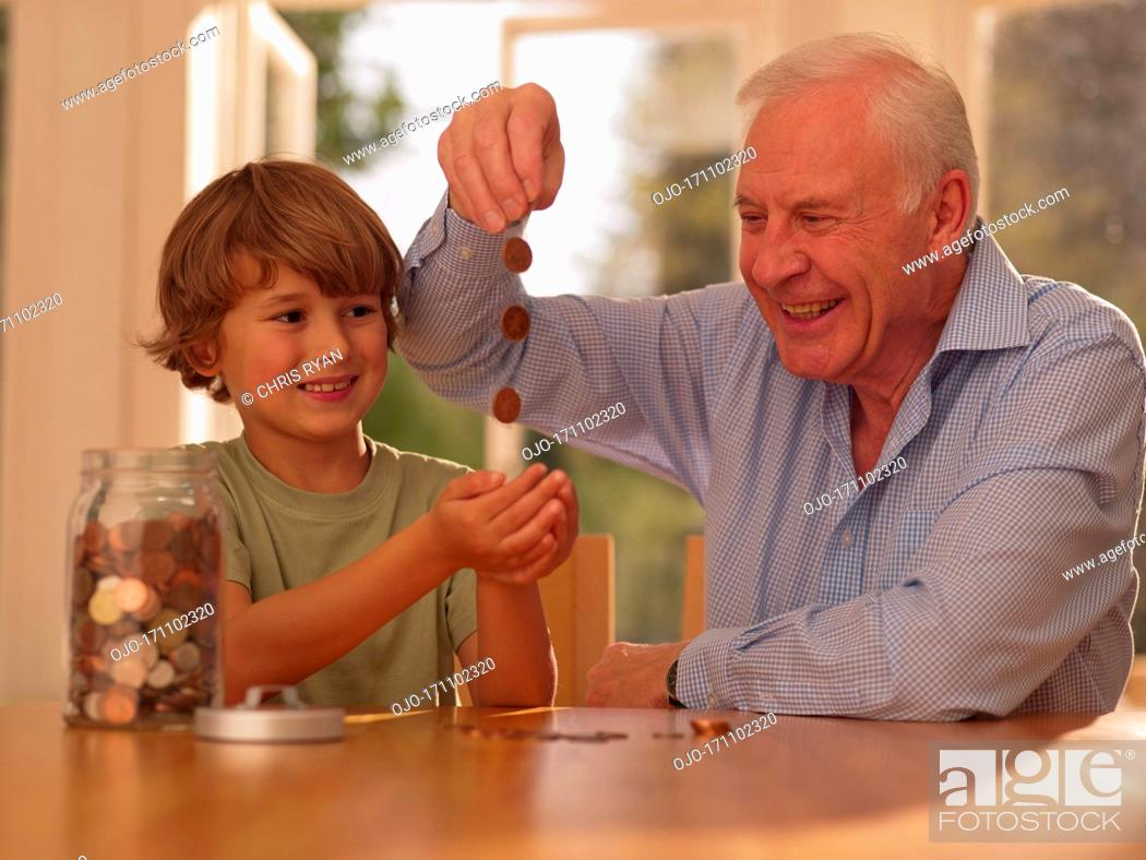 Stock Photo: Grandfather and grandson with jar of coins.
