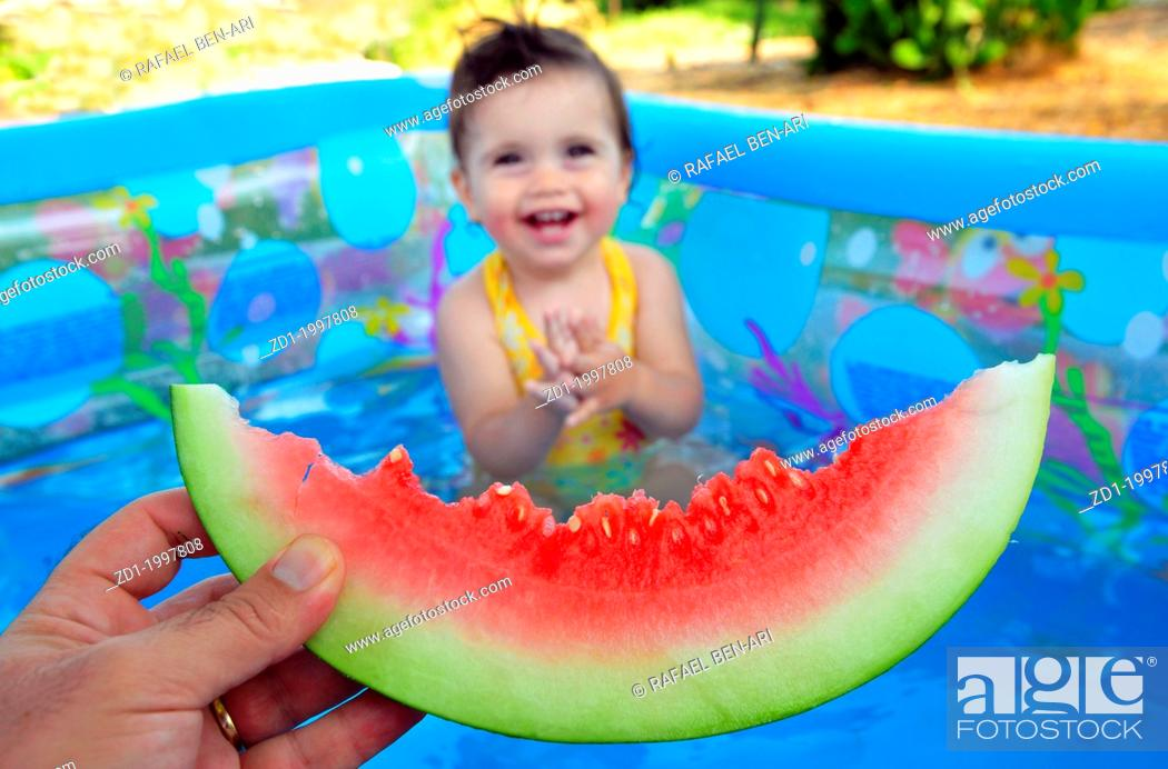 Stock Photo: A baby girl eats a cold watermelon in a baby pool in a very hot day.