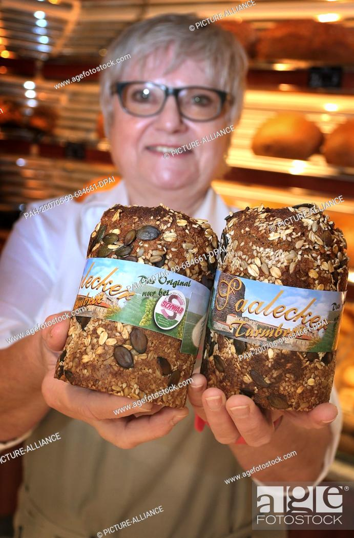 """Stock Photo: 12 June 2020, Bavaria, Hammelburg: Inge Scheller holds a barley and spelt bread baked with Franconian wine in her bakery (to dpa: """"""""Sausage."""