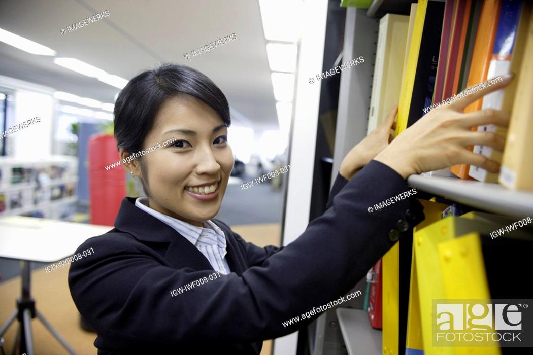 Stock Photo: A woman smiles at the camera while finding a file from the shelf.