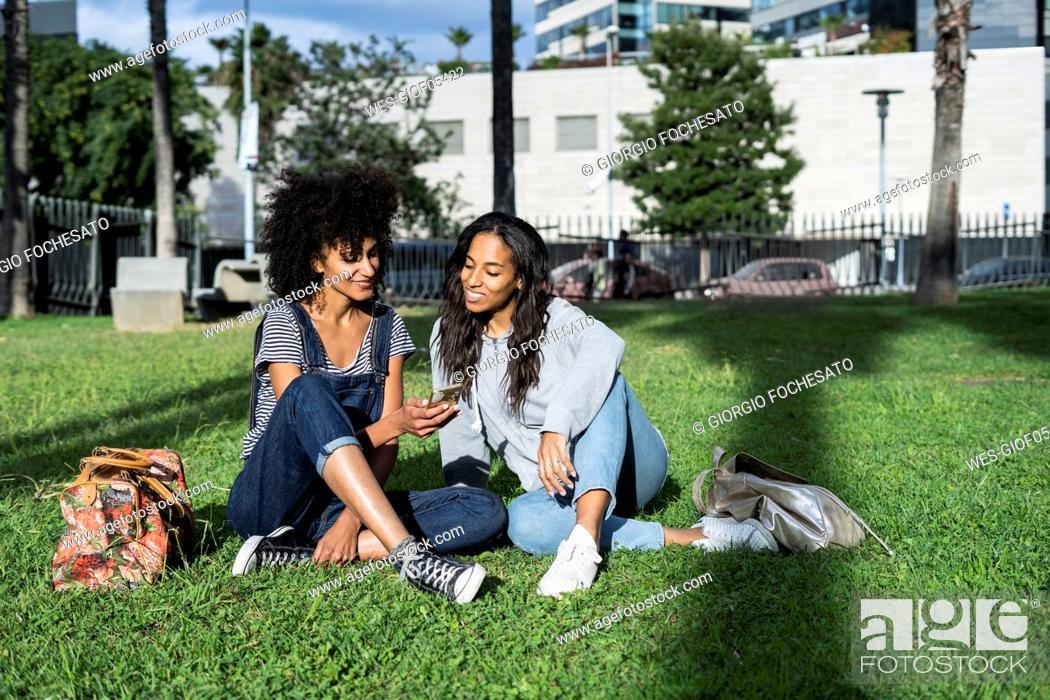 Stock Photo: Girlfriends sitting in park, having fun, using smartphone.