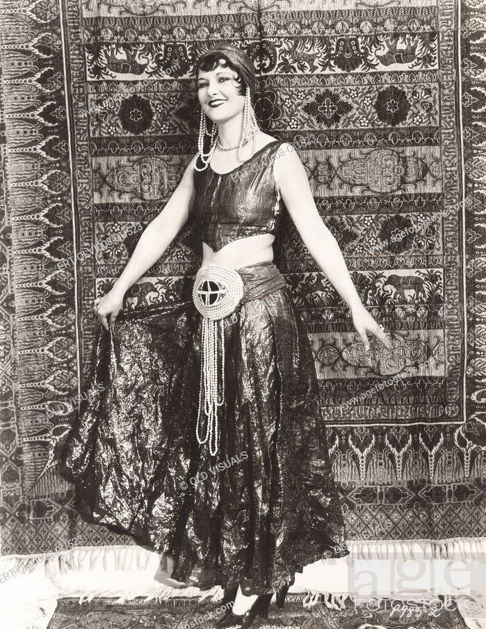 Imagen: Woman dressed in gypsy costume standing in front of rug.