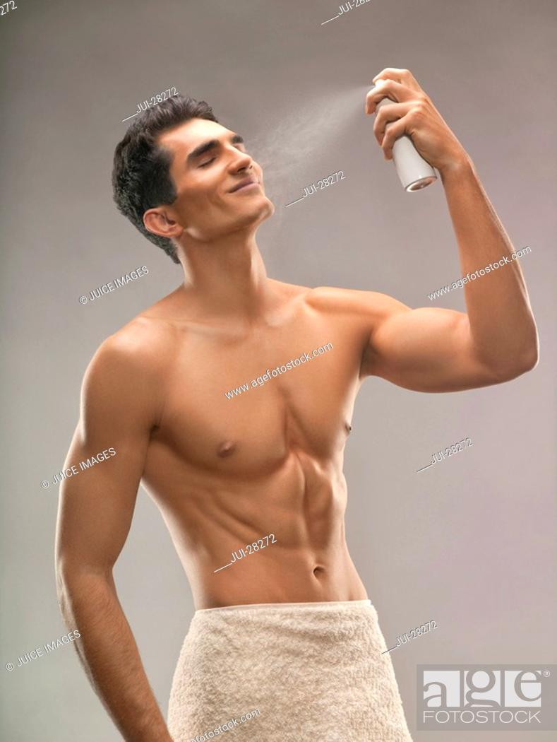 Stock Photo: Young man spraying mist on face, studio shot.