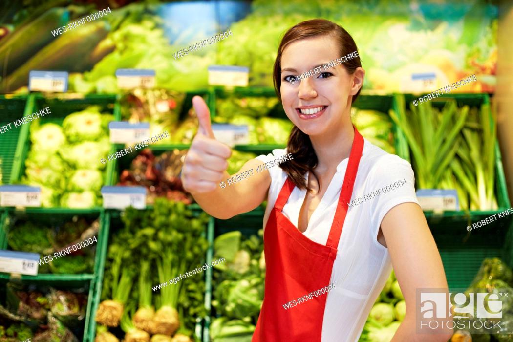 Stock Photo: Germany, Cologne, Young woman showing thumbs up in supermarket, smiling, portrait.