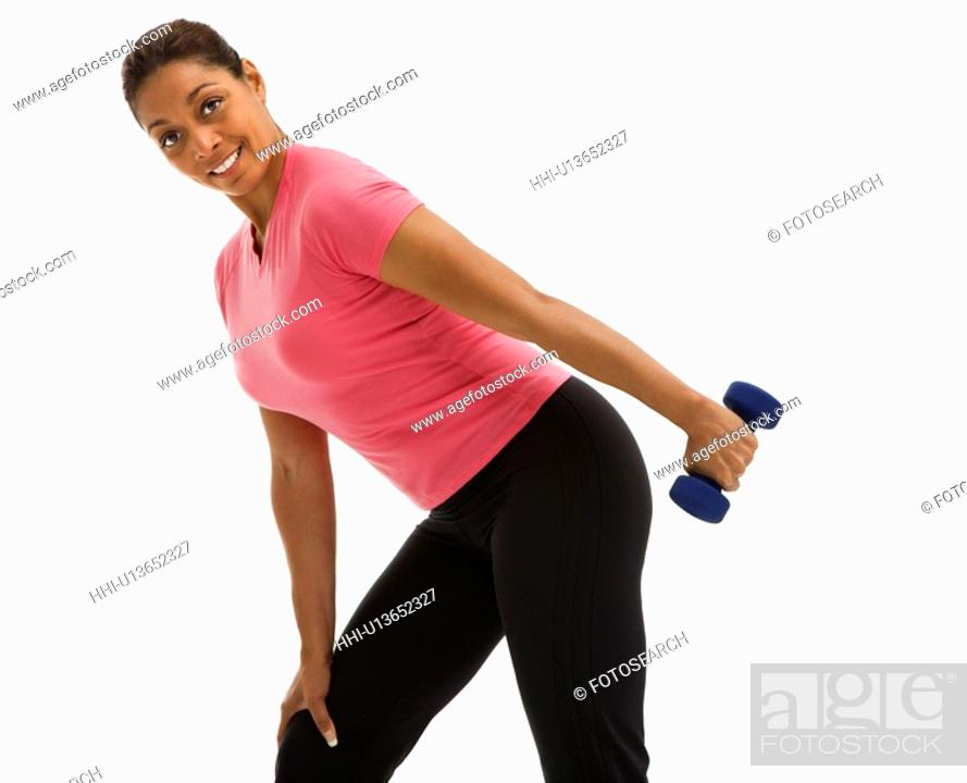 Stock Photo: Mid adult multiethnic woman exercising with dumbbell smiling and looking at viewer.