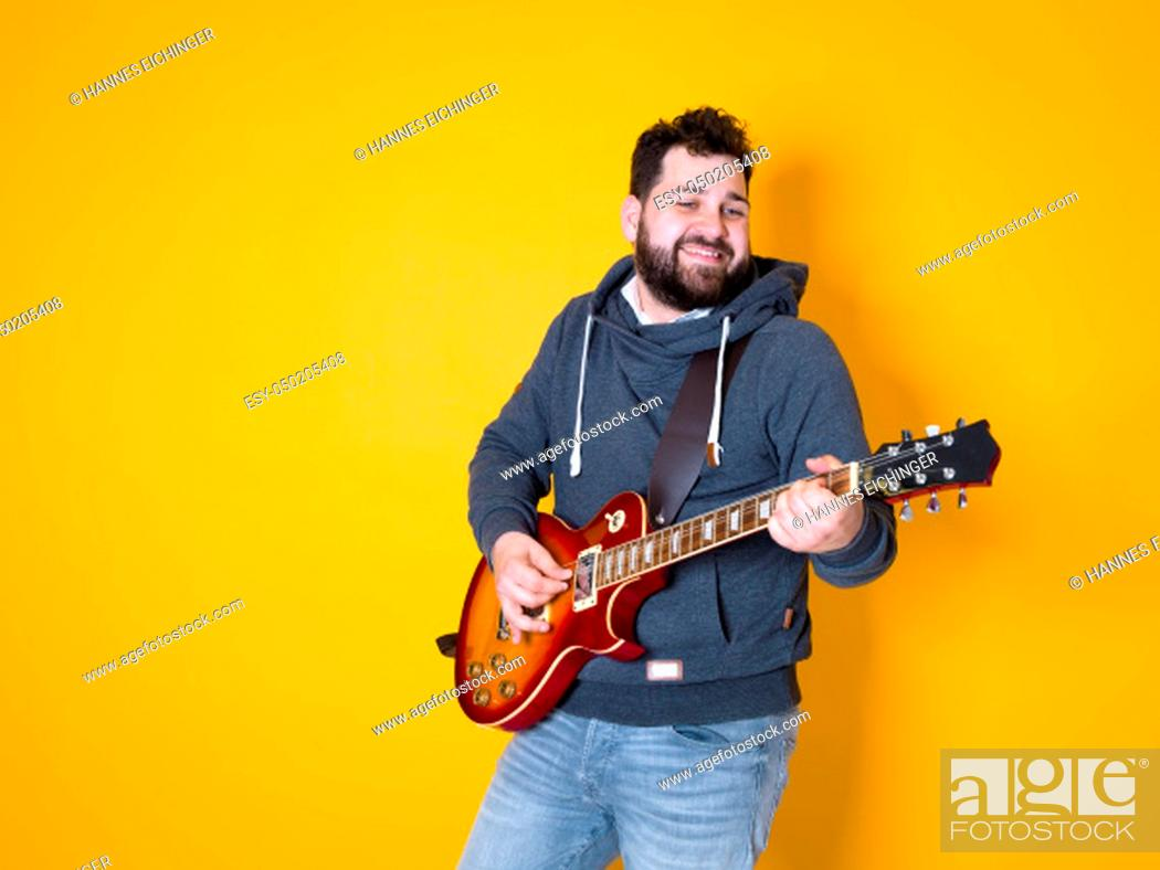Imagen: man with black hair and beard playing the electric guitar in front of a yellow background.