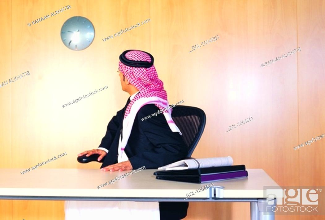 Stock Photo: Saudi Arabian businessman checking time on wall clock.