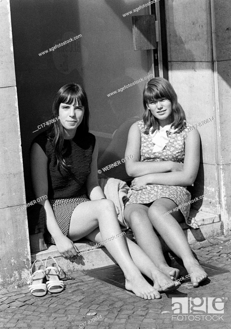 Imagen: Sixties, black and white photo, people, two young girls, aged 16 to 18 years, woman friends, girlfriends, sitting in a porchway and enjoy the sun, bare legs.