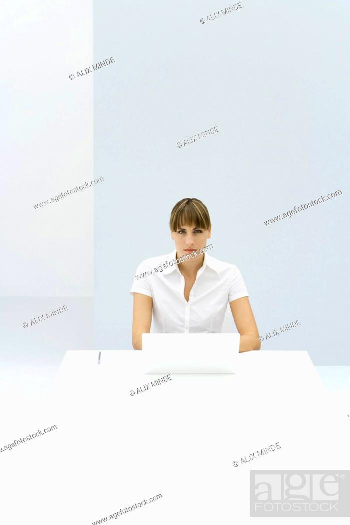 Stock Photo: Woman sitting at table with laptop, looking at camera.