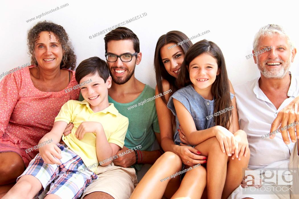 Stock Photo: Multi Generation Family Sitting Against Wall.