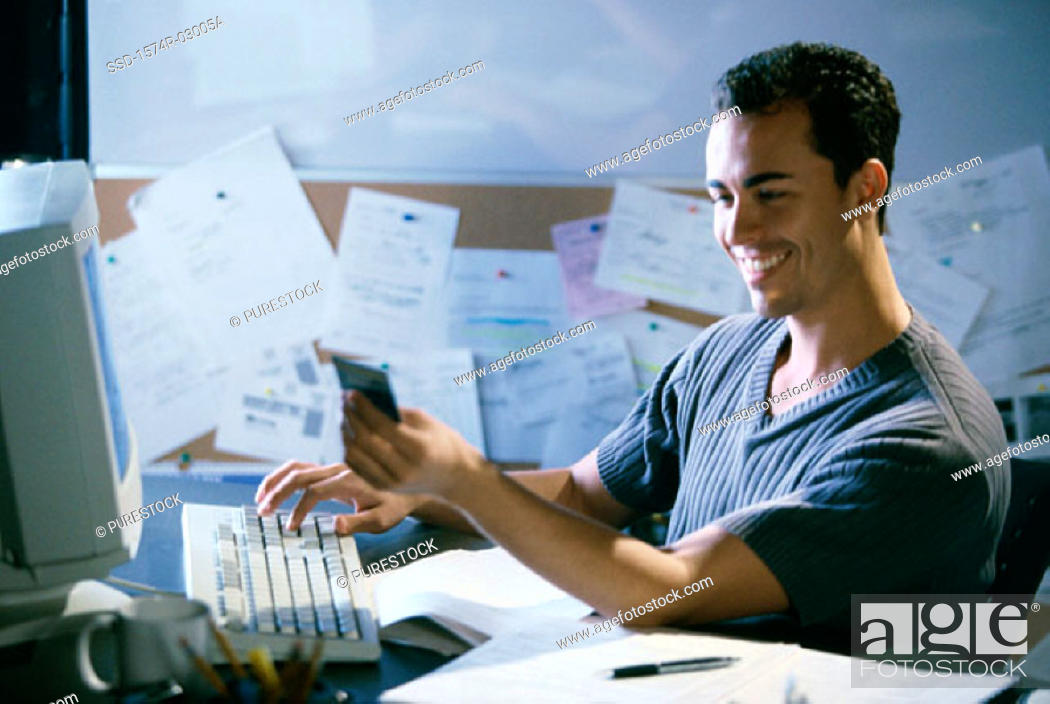 Stock Photo: Side profile of a young man working on a computer holding a credit card.
