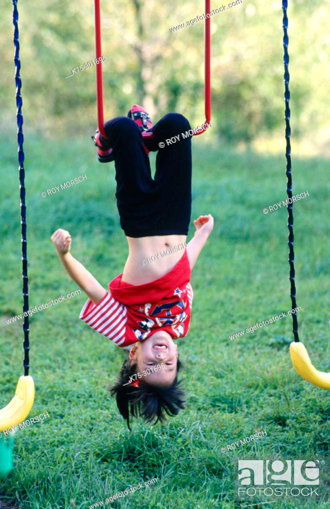 Stock Photo: Girl hanging upside down on playset.