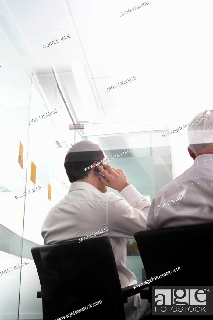 Stock Photo: Businessmen one using mobile phone sitting in office behind glass wall back view.