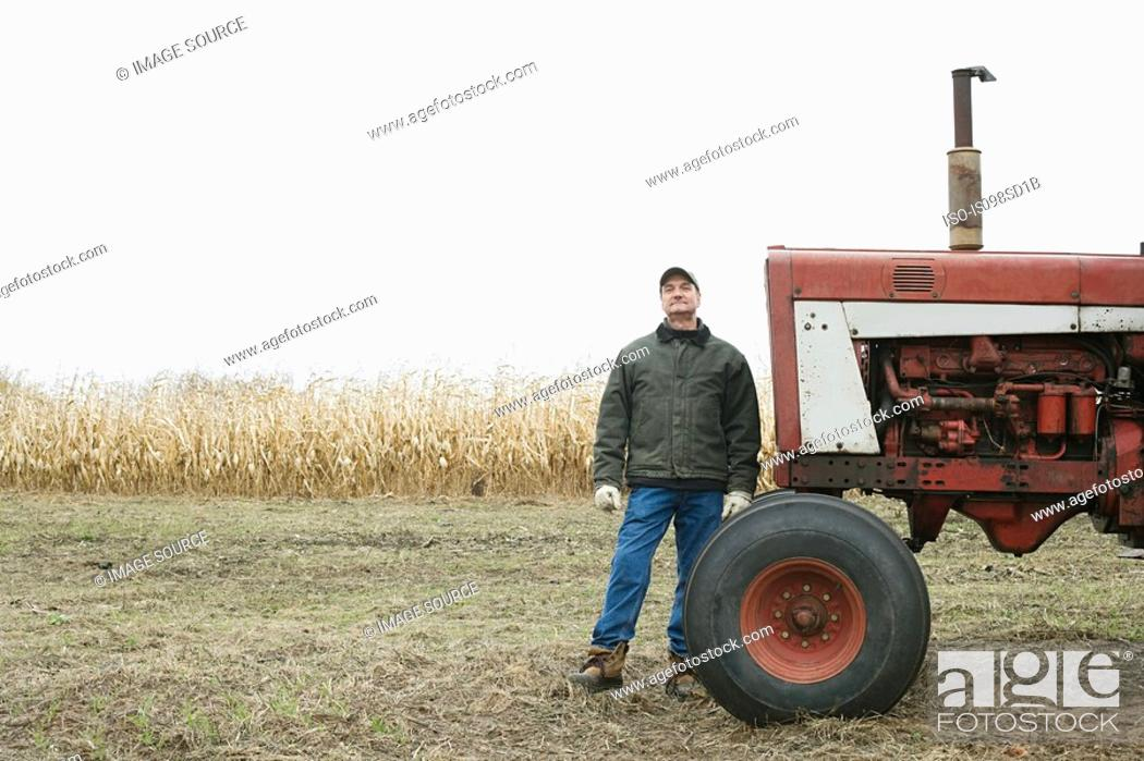 Stock Photo: Farmer by tractor.